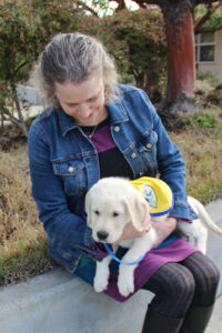 Rachel Meyer sits looking at a yellow Canine Companions puppy on her lap