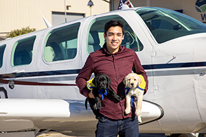 young man holding two Canine Companions puppies in front of plane