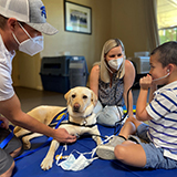 three people with a Canine Companions service dog