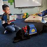child reading a book to Canine Companions service dog