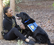 person sitting and smiling at Canine Companions service dog