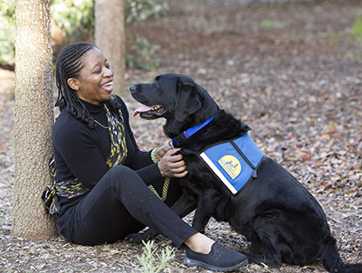 person sitting and looking at Canine Companions service dog