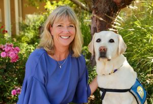 CEO Paige Mazzoni with a yellow Canine Companions service dog