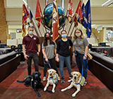 One male and three female college students stand in front of flags and a globe with one black and two yellow Labradors in yellow vests.
