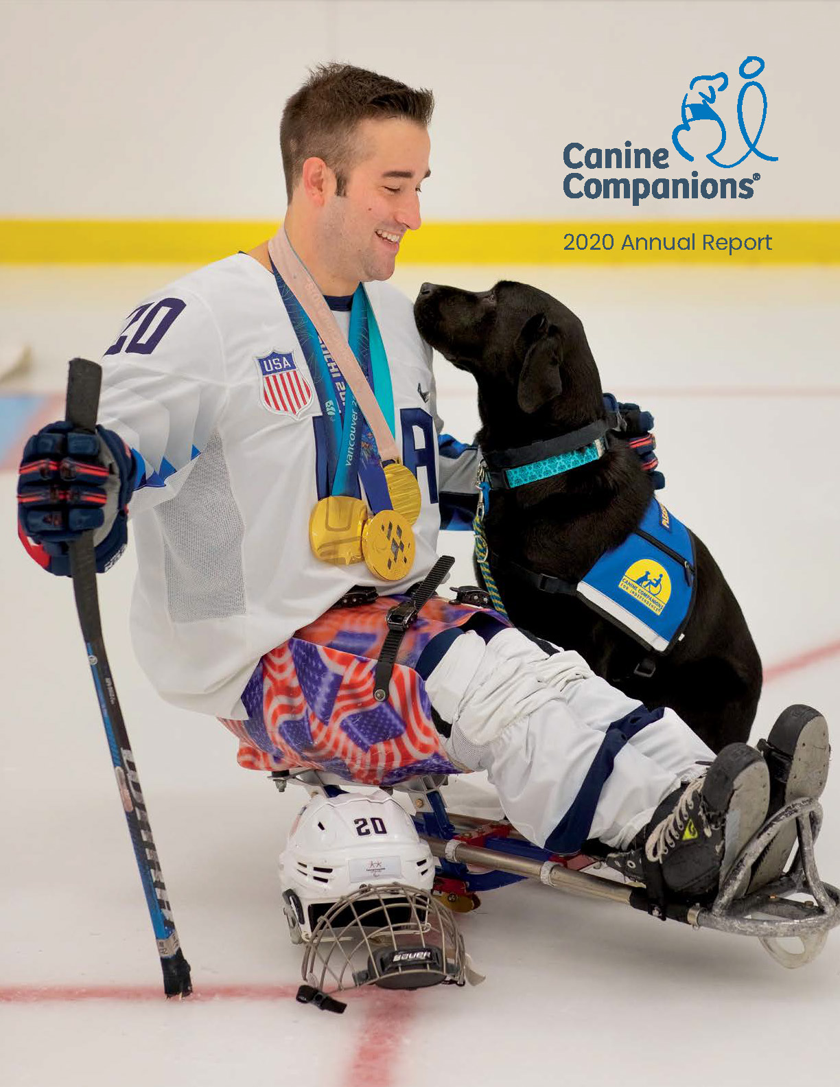 man laying on accessible skates petting and smiling at Canine Companions service dog