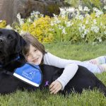 Young girl hugging Canine Companions service dog