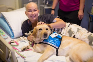 patient laying in hospital bed with Canine Companions service dog laying by their side