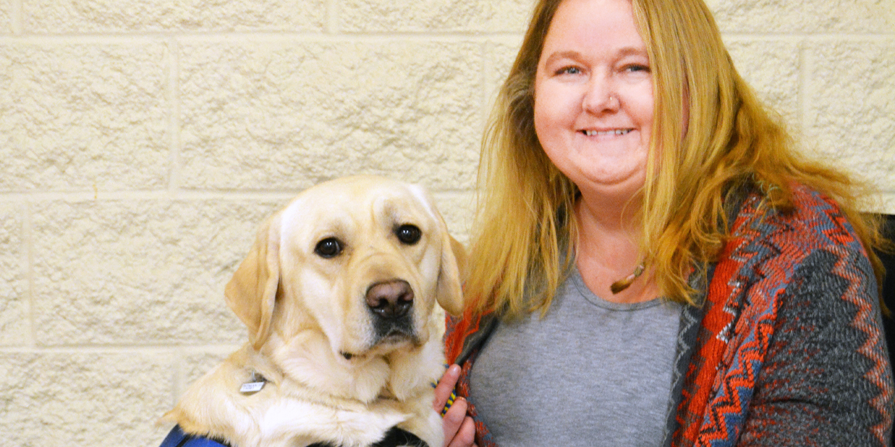 A yellow Labrador with front legs rested on woman's lap as she sits in a wheelchair