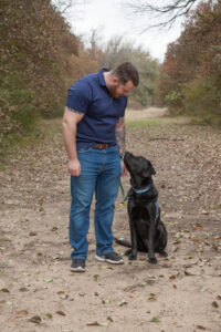 Canine Companions graduate looking at service dog by his side