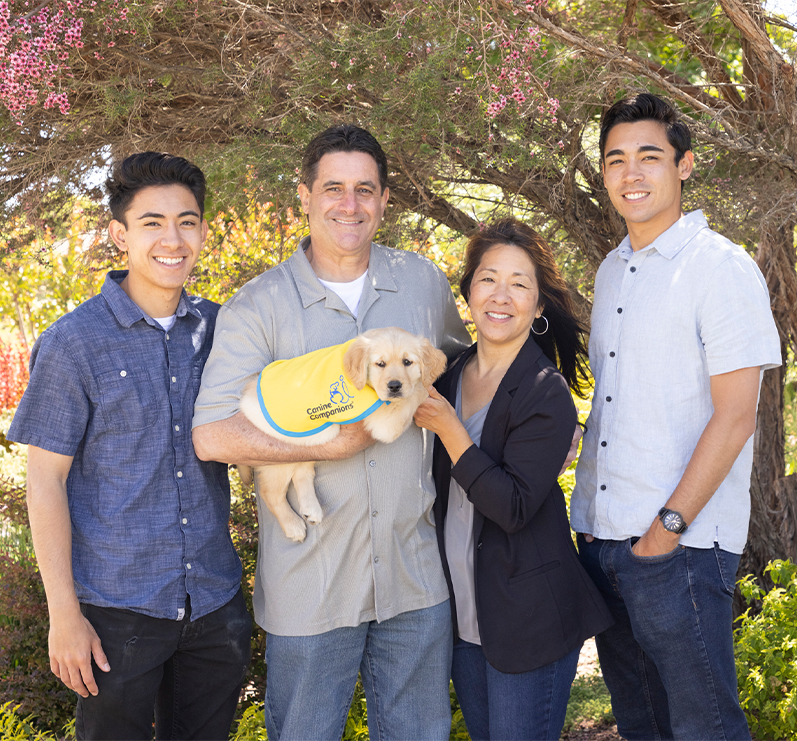 family of four holding canine companions puppy