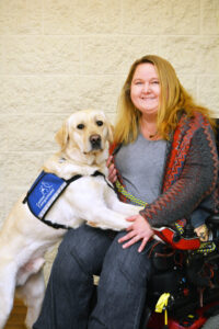 woman in wheelchair with Canine Companions service dog resting on her lap