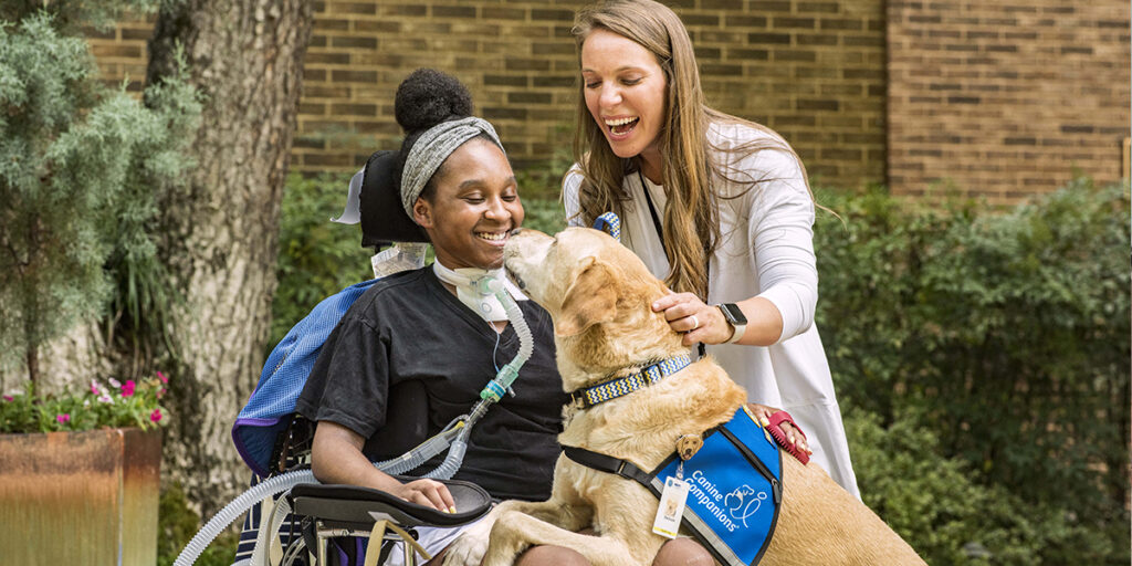Canine Companions facility dog Barboza resting on lap of patient in wheelchair