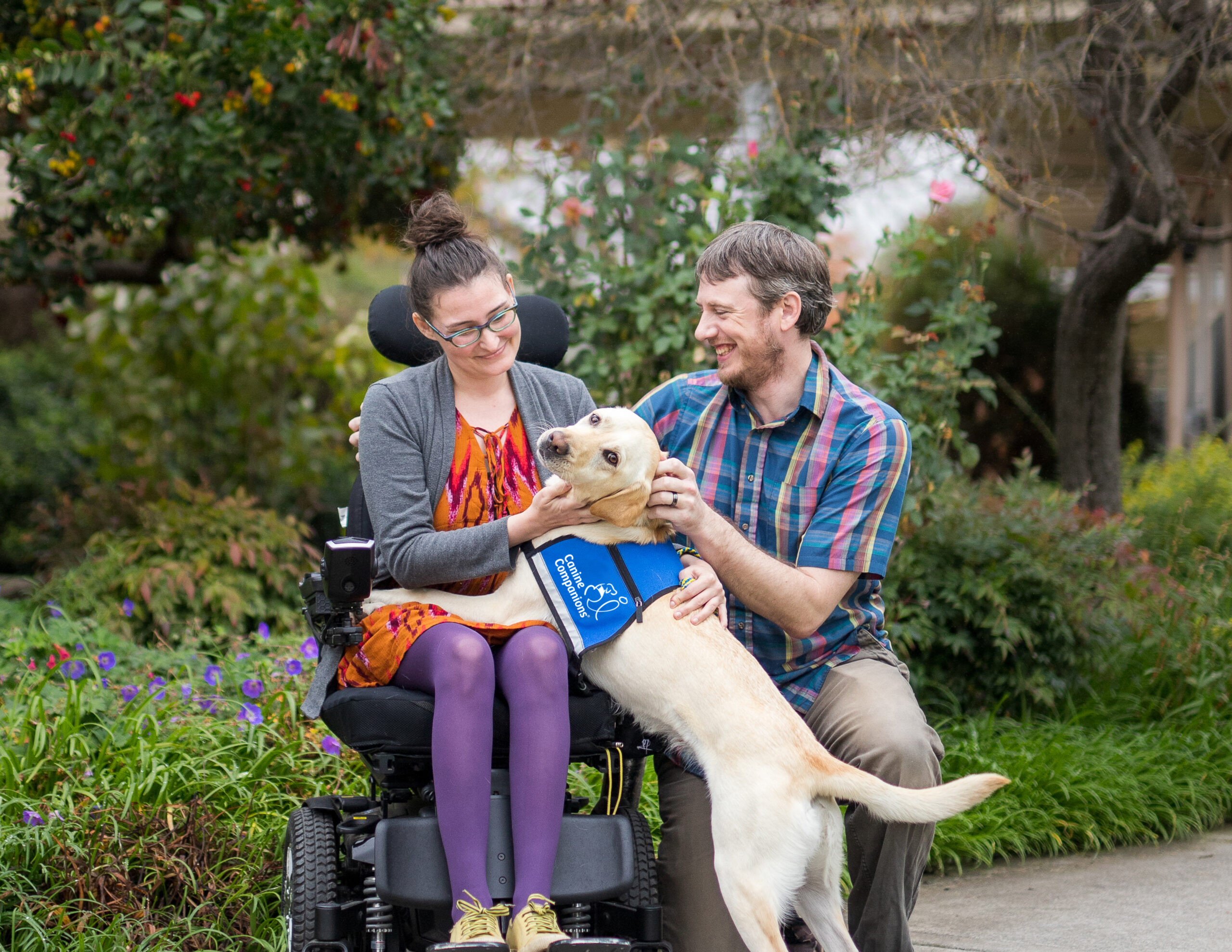 Young woman in a wheel chair with her service dog next to a young man